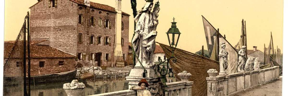 Statua della Madonna a Chioggia con vicino due bambini e delle barche nello sfondo.