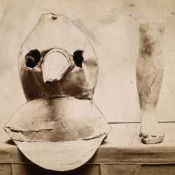 Immagine di un apparato in tela cerata per la protezione dalla peste, con a fianco un modello in terracotta di piede e gamba — (Credit: Wellcome Collection)