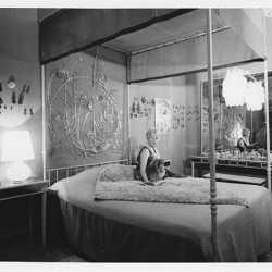 Peggy Guggenheim nella camera da letto di Palazzo Venier dei Leoni; alle sue spalle Alexander Calder, Testiera di letto in argento (1945-46, PGC); Venezia, anni '60.