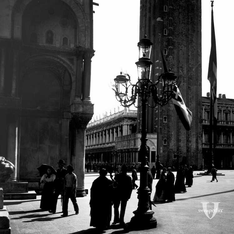 """Passanti ai piedi della Basilica marciana e sulla destra il Campanile di San Marco chiamato anche dai veneziani """"El paron de casa"""" (Brooklyn Museum)."""
