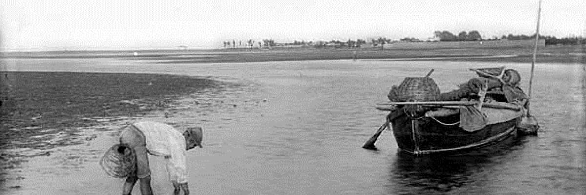 Un pescatore con la sua barchetta mentre pesca in laguna.