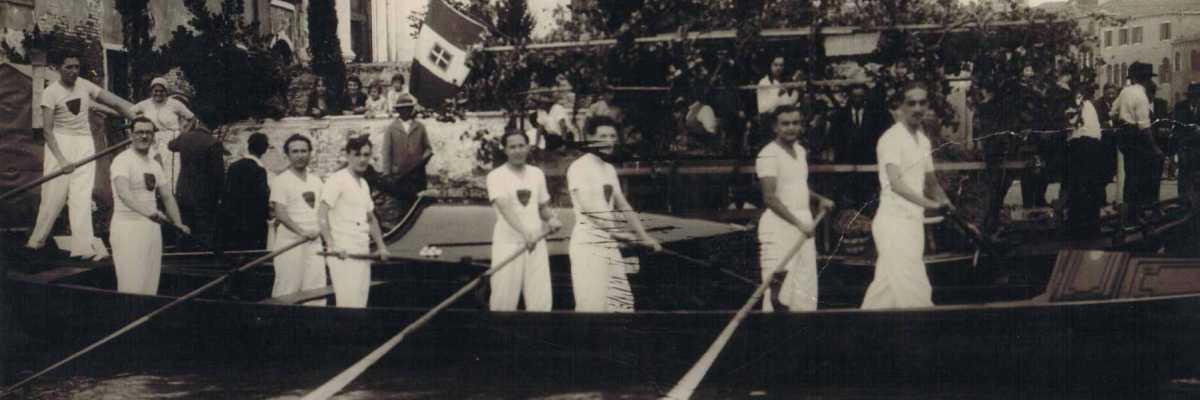 Rematori vestiti con tenuta caratteristica durante un gara di imbarcazioni.