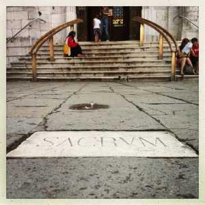 """Targa con inscritto """"Sacrum"""" verso l'entrata della chiesa omonima."""