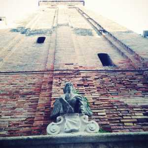 Il campanile di San Stae con l'angelo in primo piano e la cima della torre campanaria.