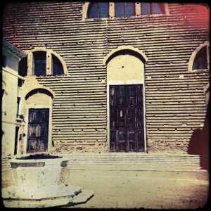 La vera da pozzo in primo piano con dietro la facciata della Chiesa di San Lorenzo.