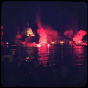 Fireworks in the water on the Giudecca canal, behind the Salute Church.