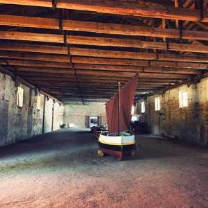L'interno restaurato dell'Ospitale, con alcune imbarcazioni tipiche. — (Archivio Venipedia/Bazzmann)