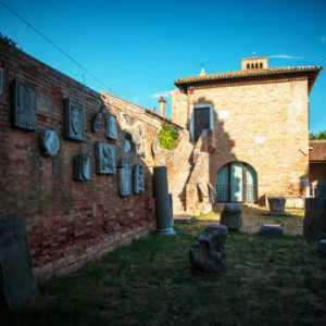 Vista laterale del Palazzo dell'Archivio con particolare del muro dove sono presenti vari reperti archeologici — (Archivio Bazzmann/Venipedia)
