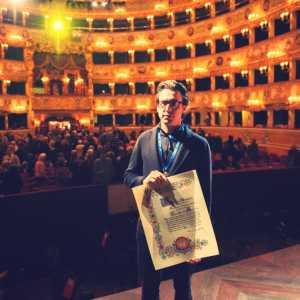 Damiano Michieletto che regge l'attestato di conferimento del premio.